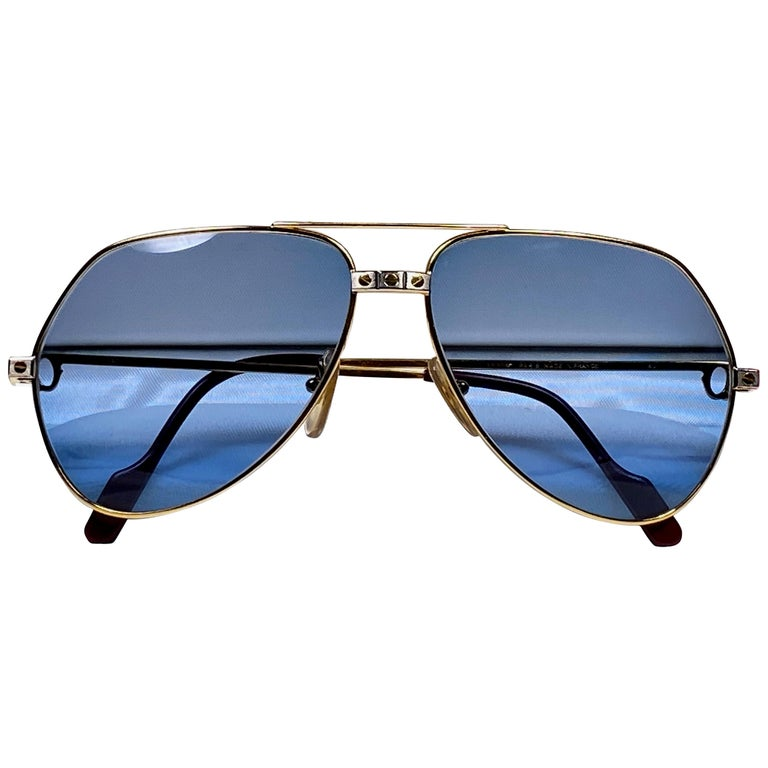 New from 1983!!! Cartier Aviator Santos Sunglasses with blue (uv protection) Lenses.  Frame is with the famous screws on the front and sides in yellow and white gold. All hallmarks. Red enamel with Cartier gold signs on the ear paddles.  Both arms