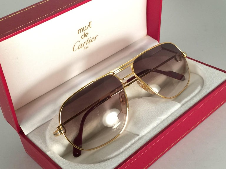 New 1988 Cartier Aviator Tank sunglasses with new honey gradient (uv protection) lenses. Frame is with the front and sides in yellow and white gold.  All hallmarks. Enamel with Cartier gold signs on the earpaddles. So classy, both arms sport the C