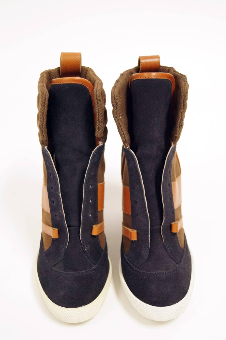 Contemporary wedge sneakers shoes by Chloe in complementary navy blue and orange. The sneakers feature a high collar and tongue, with laces reaching from the toe to the ankle. Wedge, heel, toe, and tongue are covered in navy blue suede. Ankle and