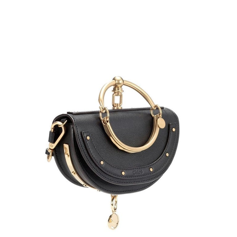Chloé's Nile Minaudière crossbody bag has the signature charm the brand is known for. Crafted from smooth beige-hued leather and accented with golden hardware, this half-moon style features a doorknob-inspired, oversized top handle for a distinctive