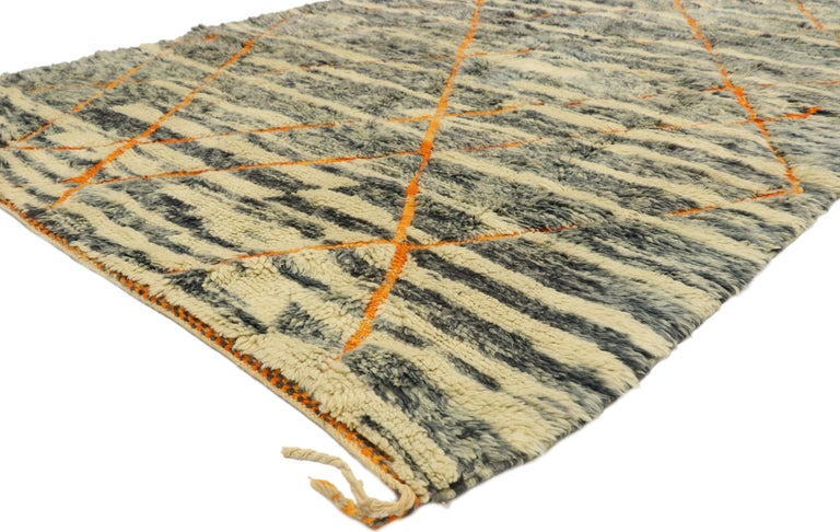 20993, new contemporary Beni Mrirt carpet, Berber Moroccan rug. This hand knotted wool contemporary Moroccan area rug features contrasting orange colored lines running the length of the abrashed cream and steel gray field. The asymmetrical lines