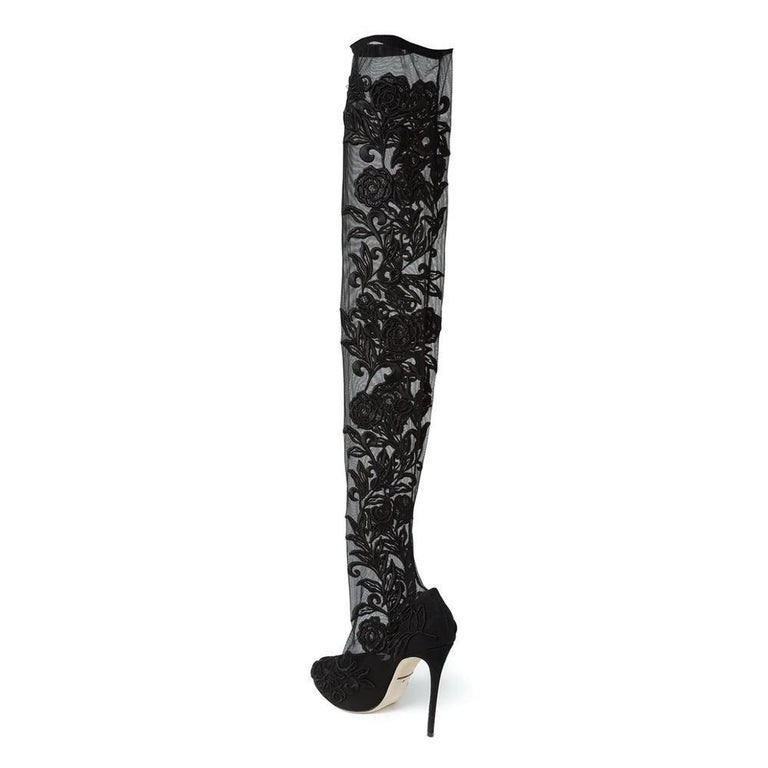 Sleek and seductive, these black cotton lace panel over the knee boots from Dolce & Gabbana are designed to make a statement. Featuring an almond toe, a pull-on style and a high stiletto heel, this dramatic pair bring a alluringly feminine touch to