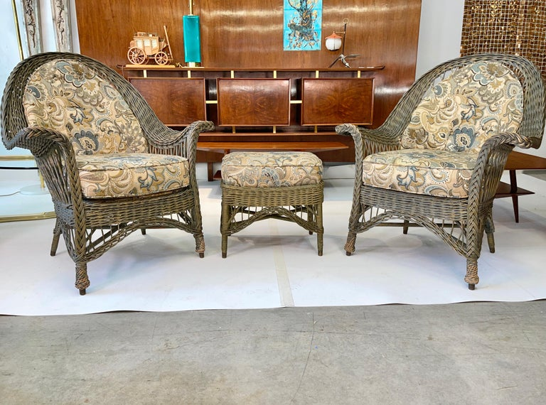 Pair of early 1920's painted wicker armchairs and single ottoman produced in Boston's old West End by New England Reed Co. 11 Greene Street. Original labels present on one chair and ottoman. Original green paint. Upholstered seat decks, seat