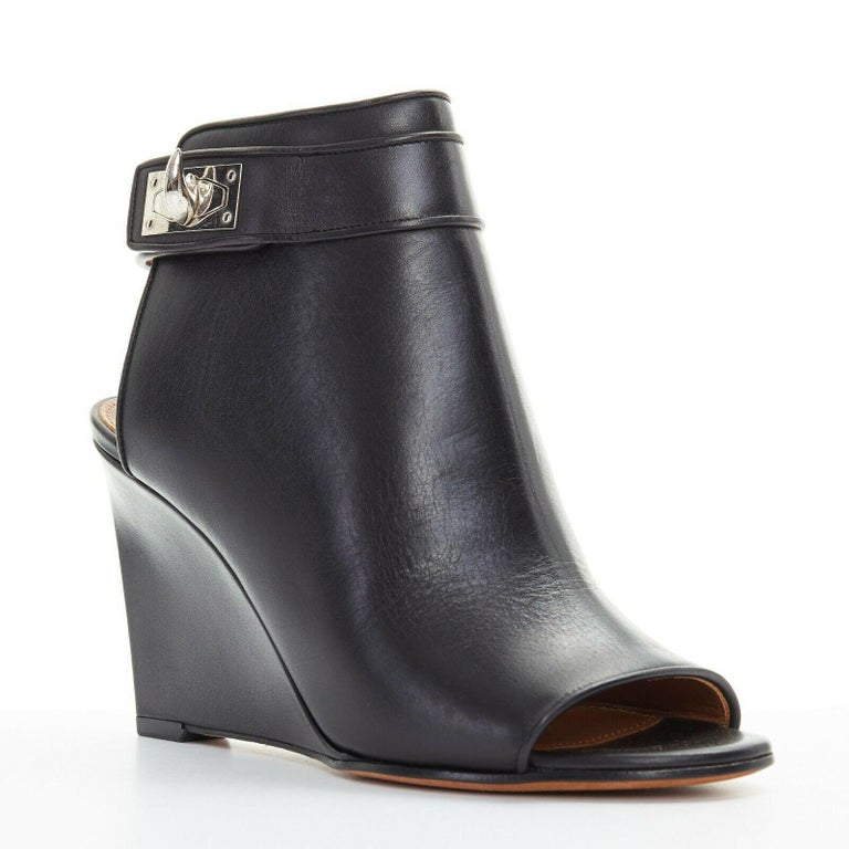 new GIVENCHY TISCI black leather peep toe silver shark tooth lock wedge EU36  GIVENCHY BY RICCARDO TISCI Black leather upper. Silver-tone hardware. Signature shark tooth twist lock ankle strao. Peep toe. Open back. Leather wrapped wedge heel. Made