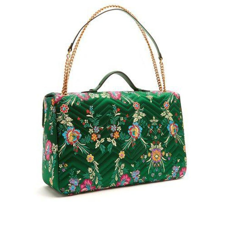 This emerald-green chevron-quilted satin style is patterned with a multicoloured floral jacquard, and embellished with an iconic antiqued gold-tone metal GG plaque on the front flap. The bubblegum-pink satin-lined interior hosts a zip-fastening