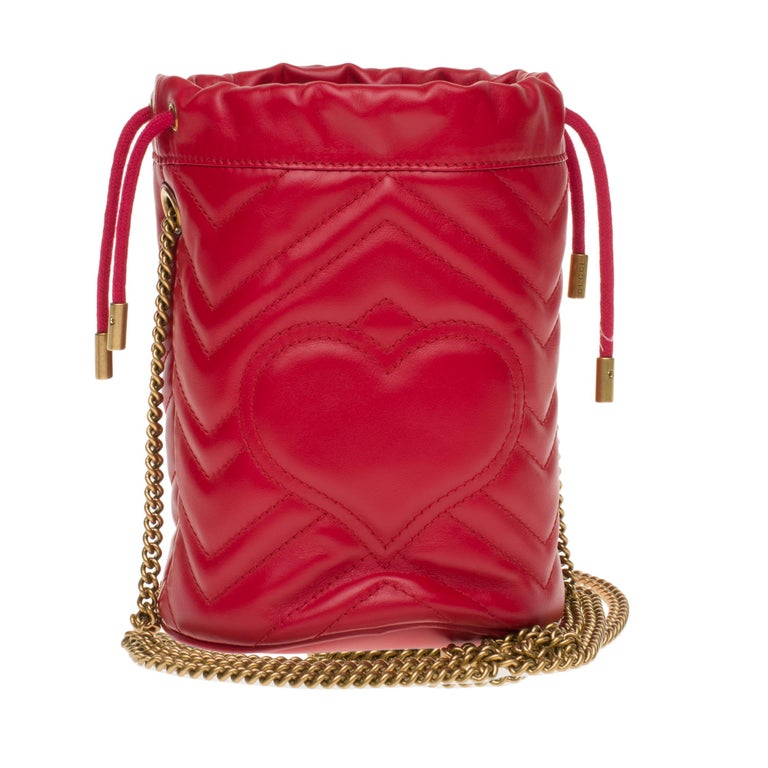 Gucci mini bucket bag GG Marmont made in red quilted leather with chevrons. Inspired by a model from the archives of the 70's, a flagship period for the House, the Double G adorns the front of this accessory. With its chain shoulder strap and