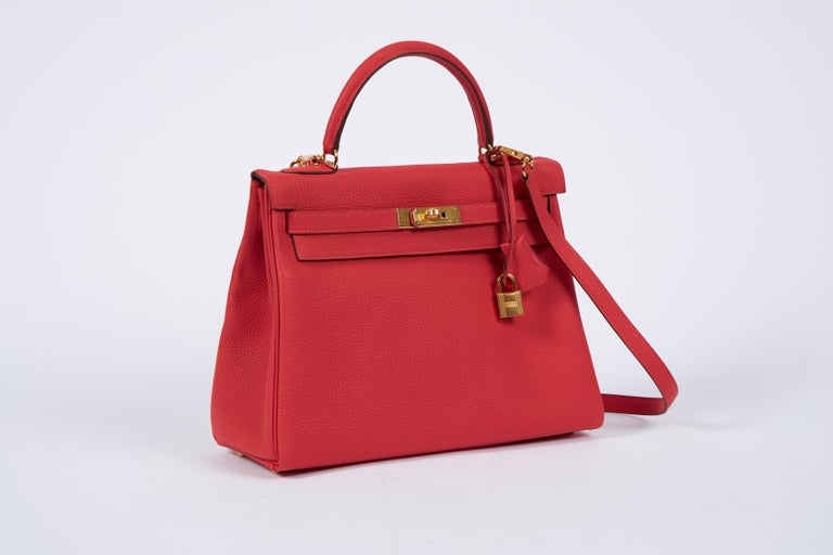 Hermès 32cm Kelly Retourne in rouge pivoine Togo leather and goldtone metal hardware. Detachable strap. Date stamp C for 2018. Brand new with full set: clochette, tirette, lock, two keys, dust cover, rain jacket, booklet, box, ribbon, and shopping