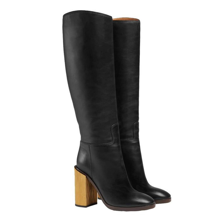 A simple knee boot with a gold galvanized heel that make you stand out from day to night. Metal Gucci logo under the arch of the Boot Color: Black (Designer: NERO 1000) Heel: Covered Gold 120 mm or 4.5