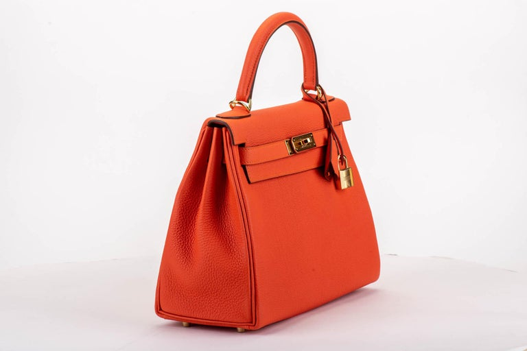 Hermes brand new in box kelly 28 retourne feu togo with gold tone hardware. Date stamp D for 2019. Comes with clochette, tirette, lock, keys, dust cover, booklet, rain jacket, box, ribbon.