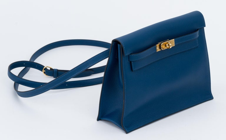 Hermes brand new in box deep blue evercolor kelly danse with gold tone hardware. The best and newest reissue of the Hermes collection, can be worn as a fanny pack, a clutch or a cross body. Blind stamp Y for 2020. Comes with booklet, felt, blacked