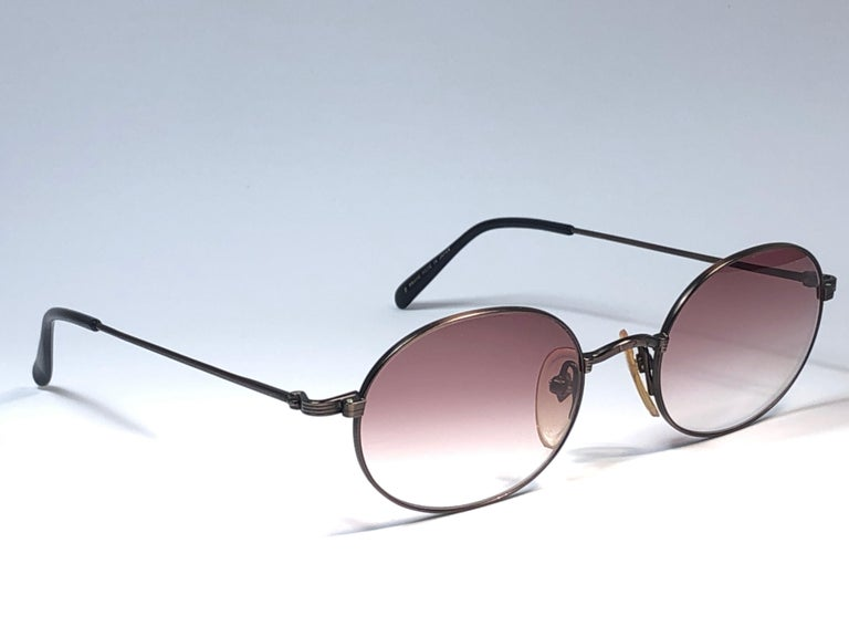 New Jean Paul Gaultier small oval dark copper frame.  Spotless light mauve gradient lenses that complete a ready to wear JPG look.  Amazing design with strong yet intricate details. Design and produced in the 1990's. New, never worn or displayed. A