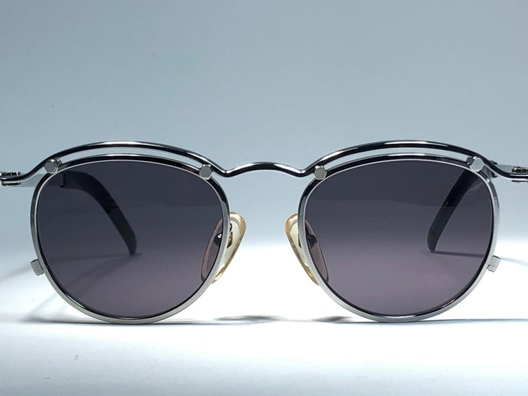 New Jean Paul Gaultier 56 8171 round gold matte frame.  Flat smoke grey lenses that complete a ready to wear JPG look.  Amazing design with strong yet intricate details. Design and produced in the 1900's. New, never worn or displayed.  The item may