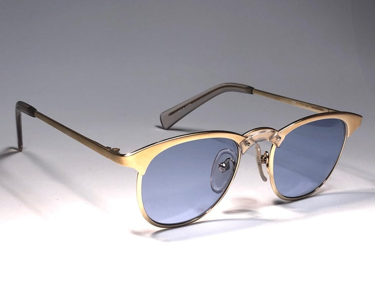 New Jean Paul Gaultier medium gold  frame.  Spotless light blue lenses that complete a ready to wear JPG look.  Amazing design with strong yet intricate details. Design and produced in the 1990's. New, never worn or displayed. This item may show