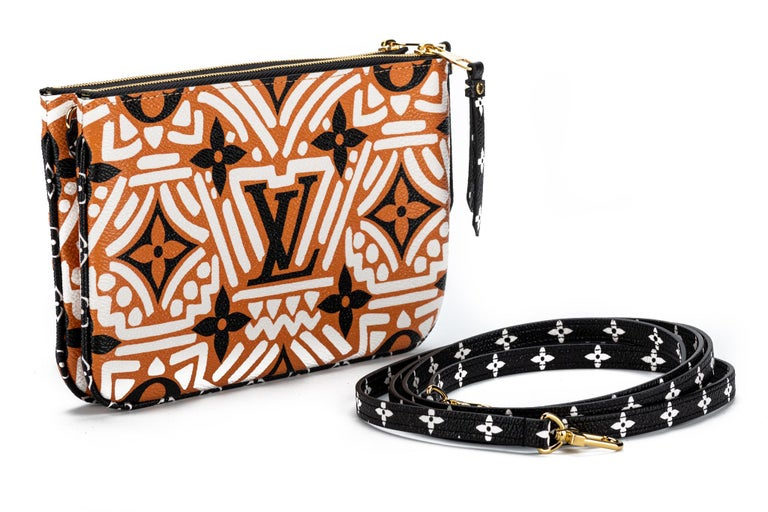 Louis Vuitton limited edition tribal coated canvas double zipper cross body bag. Multiple pockets and removable straps. Brand new with dust cover and box.