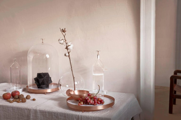 New Moon is a blown glass bell with a tray in Carrara marble and copper. This object is part of the Lunar Landscape collection designed by Elisa Ossino, who created a collection of tableware for Paola C., revisiting the classic themes of mise en