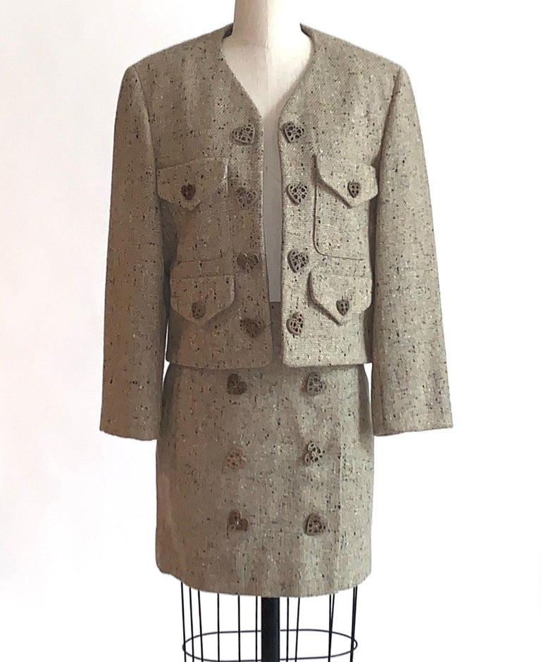 Vintage Moschino Cheap & Chic 1990s skirt suit in oatmeal tweed, speckled with flecks of orange, charcoal, and a very subtle pale lime. Open front jacket features front pockets with flaps and wooden heart buttons. Light padding at shoulders. Wrap