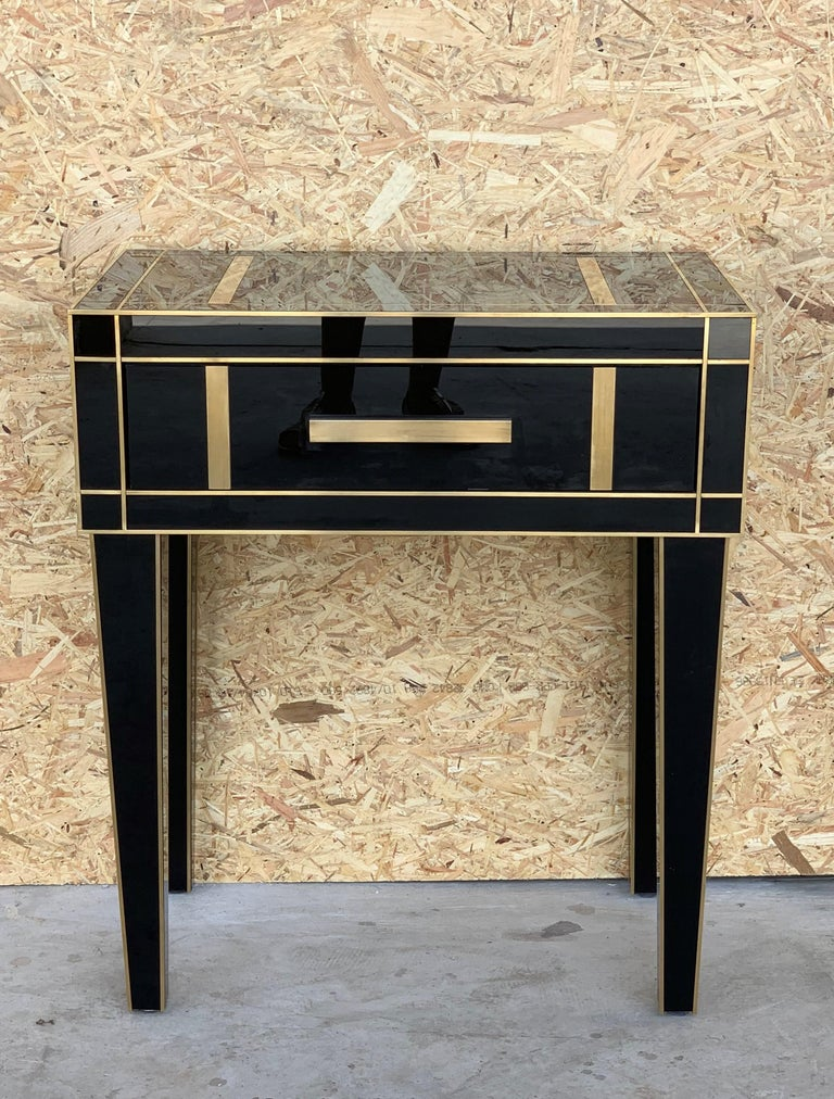 New pair of mirrored nightstands in black mirror and chrome. Beautiful pair of nightstands with mirrored finished drawers. Brass handle.