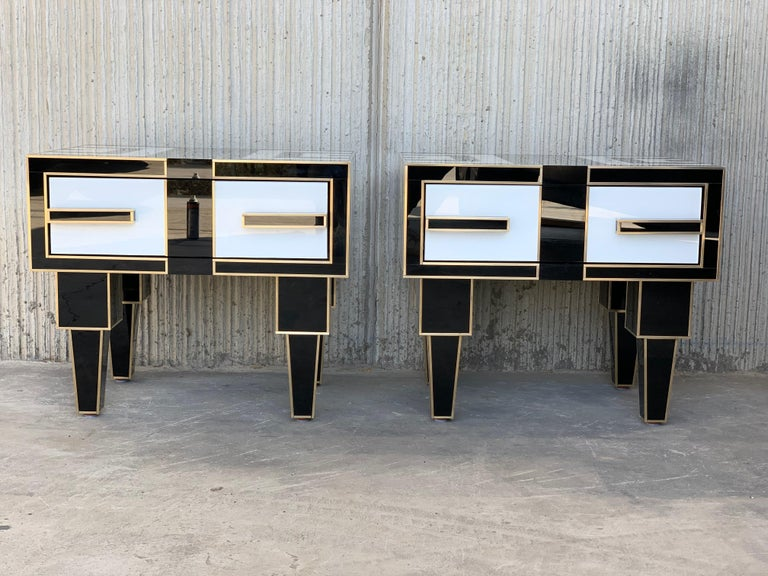 New pair of mirrored and brass nightstands with one-drawer in black and white, 20th century Two glass handles Beautiful interior details in mirror.