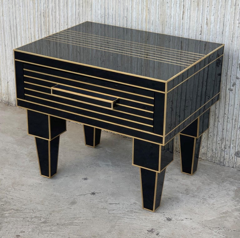 New pair of mirrored nightstands in black mirror and chrome. Beautiful pair of nightstands with mirrored finished drawers and brake stop. Glass and brass handle.