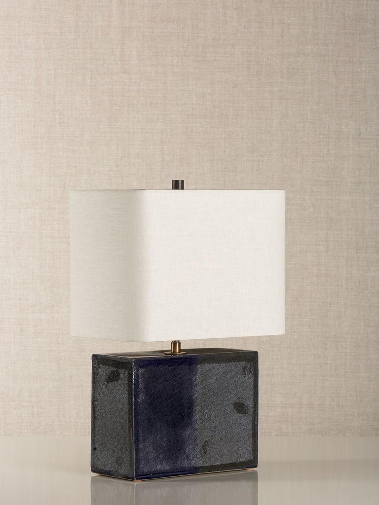 Handmade stoneware slab construction. Lamps are individually crafted and one of a kind.  Finish  Navy glaze. Antique brass fittings with dimmer switch on socket and a braided black cloth cord. Available with an off-white linen
