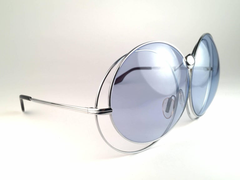 Superb. Rare Collectors Item New Vintage Christian Dior Oversized 1970's Sunglasses.   Interlocked silver metal oversized frame holding a spotless pair of celest blue lenses.  Made in Germany.   Produced and design in 1970's.  New, never worn or