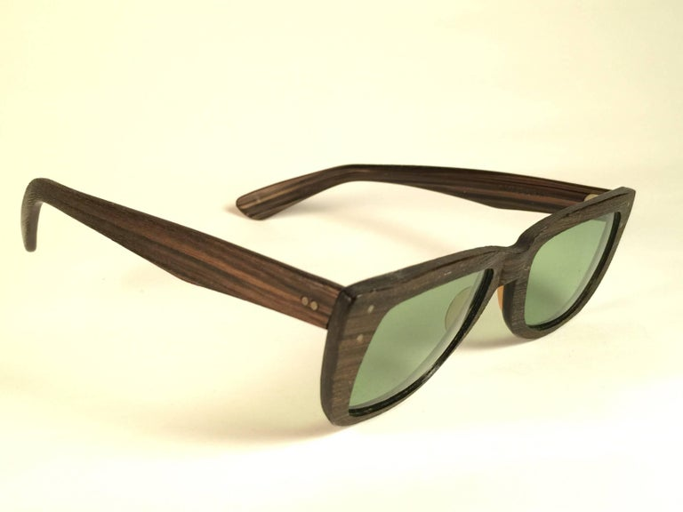 Super Rare 1960's Caribbean in dark wood with thinner and elongated temples .   Bausch and Lomb USA Made. RB3 Green lenses. Straight out of the 1960's. All hallmarks. Minor sign of wear due to 60 years of storage. A Piece of sunglasses history.