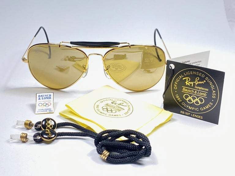 New, rare and sought after Vintage Ray Ban Olympic Series 1992   62Mm outdoorsman gold frame holding a pair of RB50 B&L etched lenses with Olympic rings logo.  Comes with a original leather Ray Ban case, carton case, cord with olympic badges and