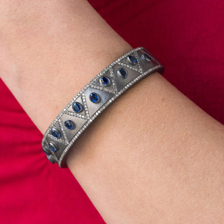 Bangle bracelet in silver, grayed and matified. Rigid, this silver bracelet is adorned on its top with herringbone patterns set with diamonds including on the borders. 11 oval blue closed- set cyanites separate these motifs. The interior is