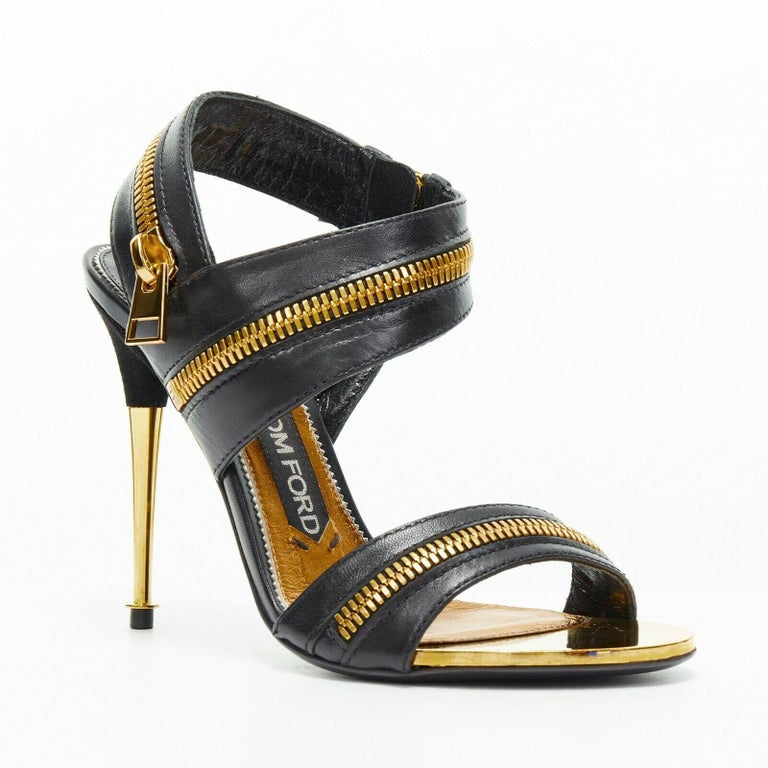 new TOM FORD black gold XL zipper design dual strap metal pin heel sandal EU36  TOM FORD Black leather upper. Gold-tone hardware. Zipper design. Large decorative zipper pull. Open toe sandals. Metal trimming at toe lining. Metal pin heel. Zipper