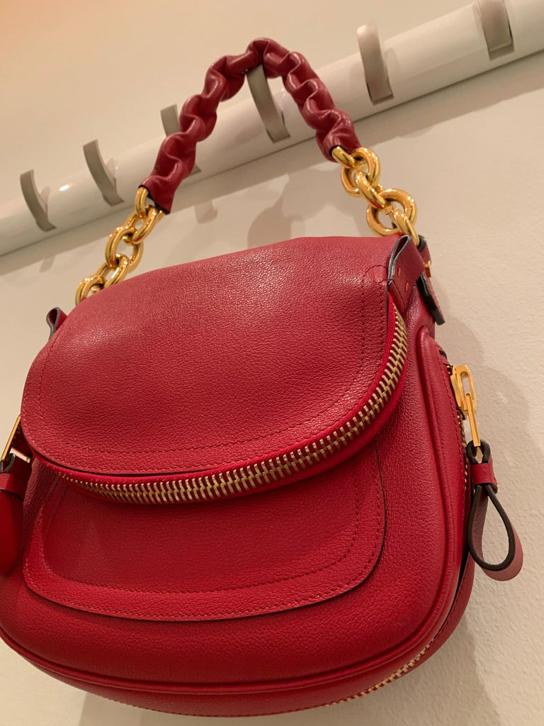 A fabulous new-never used Tom Ford crimson textured leather saddlebag-styled shoulder bag with heavy gold chain handle.  Handle at grip has leather molded around chain for comfort.  Saddle flap is a zippered pocket.  Originally purchased at Bergdorf