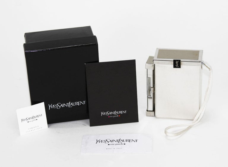 Tom Ford for Yves Saint Laurent  Spring/Summer 2001 Collection An Yves Saint Laurent white silk cigarette case and lighter. This item features a chrome tone latched hinged top that opens to a space suitable for a pack of cigarettes. Another latched