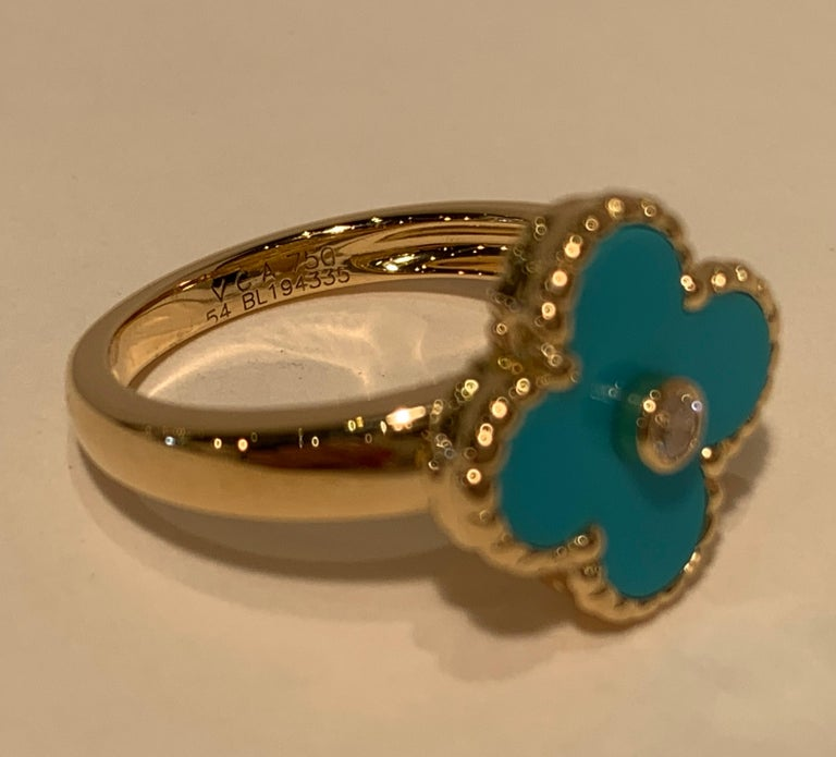 Exquisite authentic Van Cleef & Arpels 18 karat yellow gold ring of unparalleled artistry features a bright blue turquoise 4 leaf clover shaped face with a bezel set round brilliant diamond center stone. The turquoise is bezel set with beaded trim