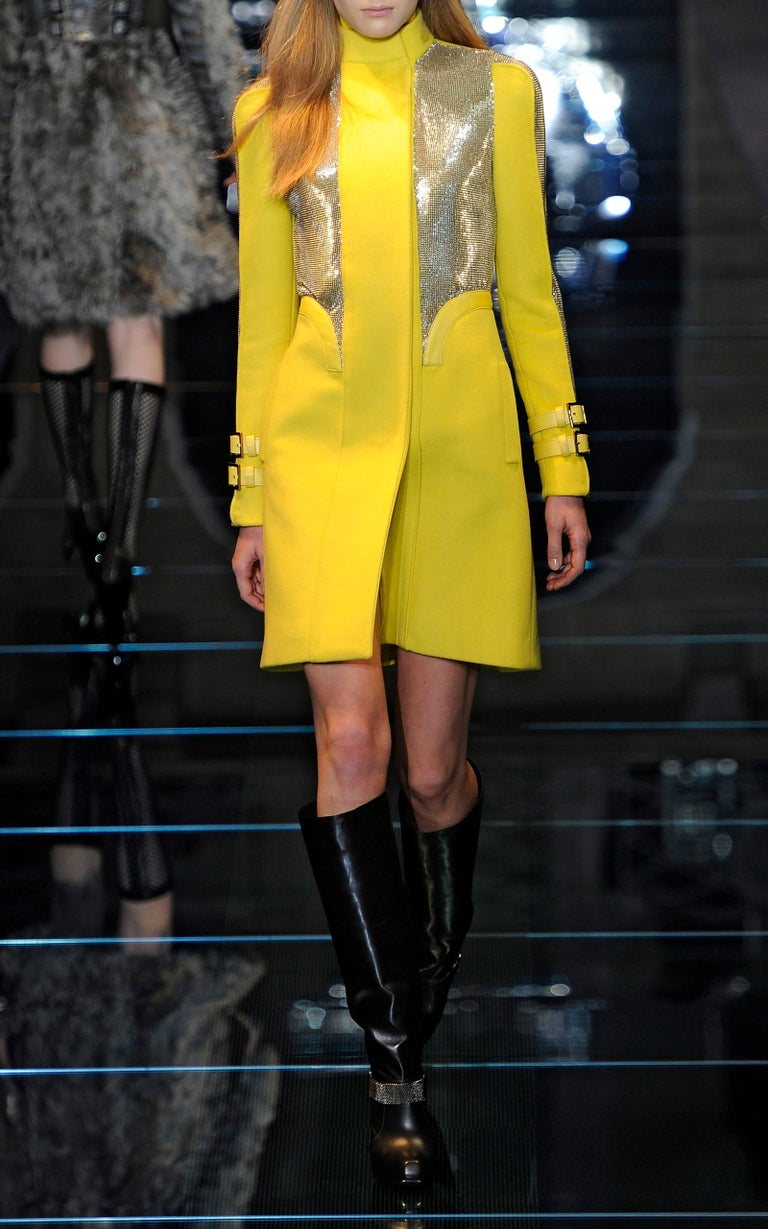 New Versace Chain Mesh Panel Yellow Wool Coat Designer size 38 - US 4 This bright yellow coat features geometric shaped front chain mesh panels and a mock turtleneck collar. Hidden front snap closures, two side pockets, leather adjustable buckles.
