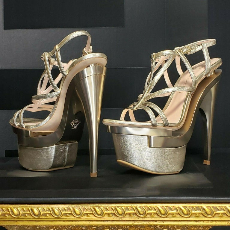 Versace Platform Sandals  Heel measures approximately 180mm/ 7 inches with a 65mm platform.   Footwear doesn't get more fabulous than Versace's   vertiginous gold leather sandals.   Daringly crafted with a layered cutout platform, they'll guarantee
