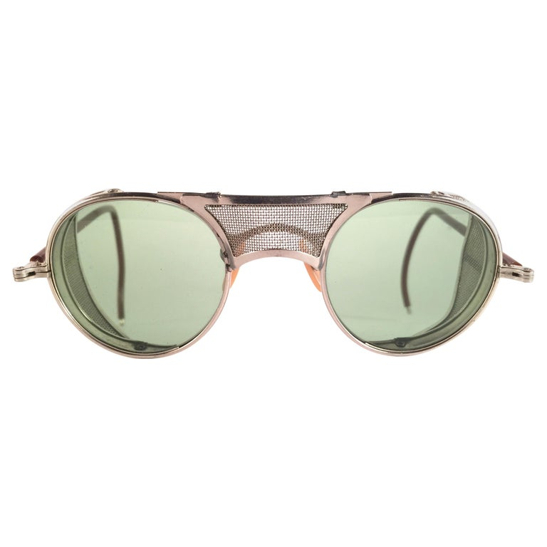 Superb Item!   1950's Bausch & Lomb Safety Goggles. Folding silver metal side cups and special wrapped temples. Mint true green round lenses.   A beautiful piece of sunglasses history.