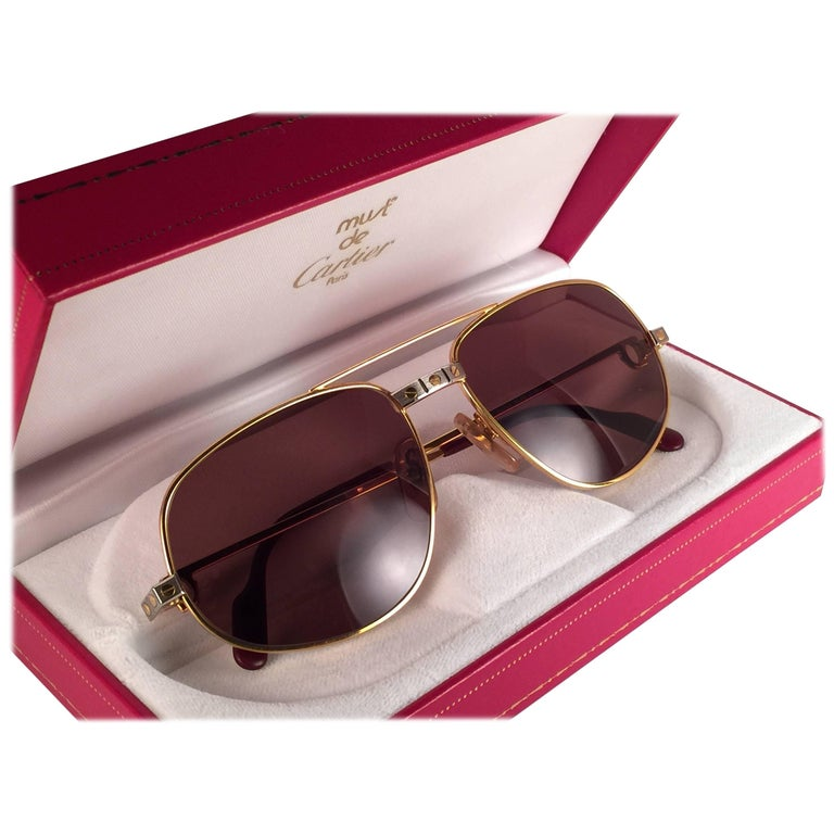 Vintage Cartier Romance Santos sunglasses with the honey brown (uv protection)lenses.  Frame is with the front and sides in yellow and white gold. All hallmarks. Red enamel with Cartier gold signs on the ear paddles. Both arms sport the C from