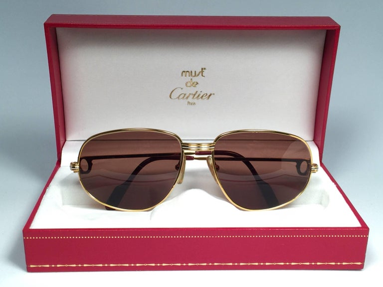 Vintage Cartier Romance Vendome sunglasses with solid brown  (uv protection)lenses.  Frame is with the front and sides in yellow and white gold.  All hallmarks.  Red enamel with Cartier gold signs on the ear paddles. Both arms sport the C from