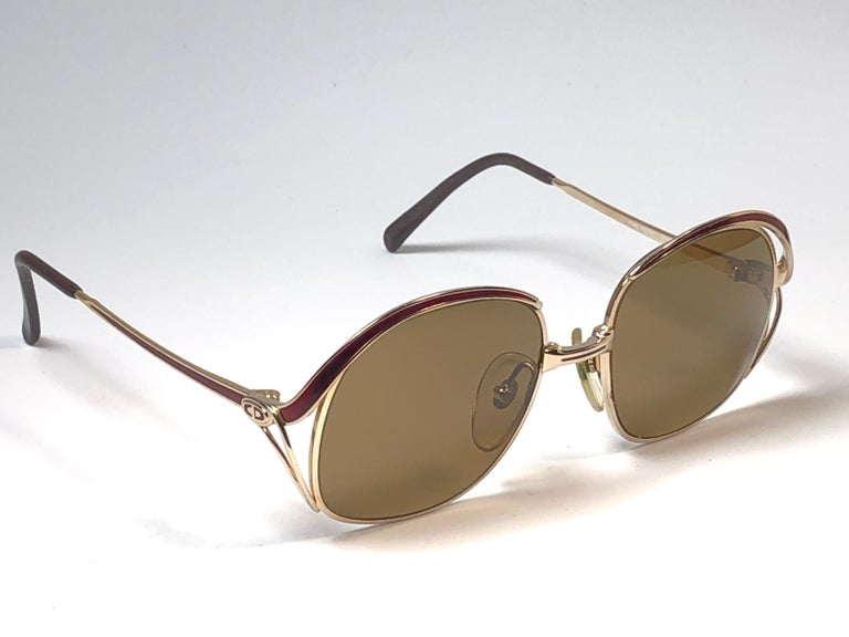 New vintage Christian Dior sunglasses. Burgundy enamel details over a gold frame.  Grey lenses.  Comes with it original CD sleeve.  New, never worn or displayed this item may show light sign of wear due to storage.  Made in Austria