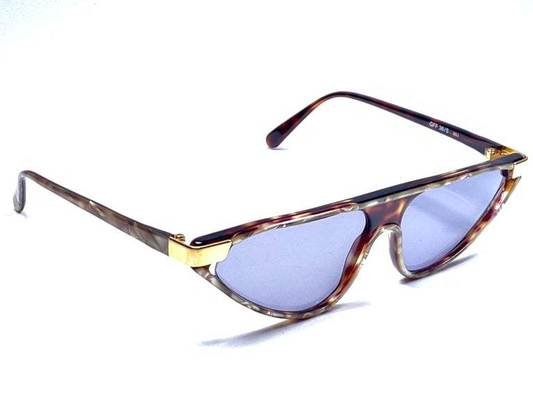 New vintage Gianfranco Ferre sunglasses.      Gold and tortoise details frame holding a pair of spotless grey lenses.     New, never worn or displayed.    Made in Italy.  MEASUREMENTS     FRONT : 15 CMS  LENS HEIGHT : 3.5 CMS  LENS WIDTH : 6 CMS