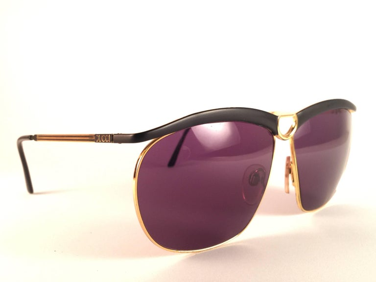 New Vintage Gucci Sunglasses in sleek black with gold details frame. Spotless purple lenses.   New never worn or displayed. This item could show minor sign of wear due to nearly 30 years of storage. Made in Italy.
