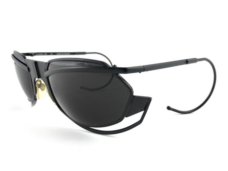 Precious limited edition IDC G1 Pour Marithe Francois Girbaud Black mate sunglasses holding a spotless pair of dark grey lenses. Curled temples for a fashionable yet comfortable wear.  New, never worn or displayed. This pair could show minor sign