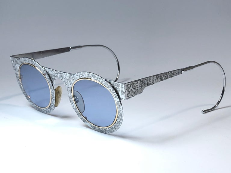 IDC Pour Marithe Francois Girbaud round silver with engraved accents sunglasses holding a spotless pair of Lligh lenses. Curled temples for a fashionable yet comfortable wear.  New, never worn or displayed. This pair could show minor sign of wear