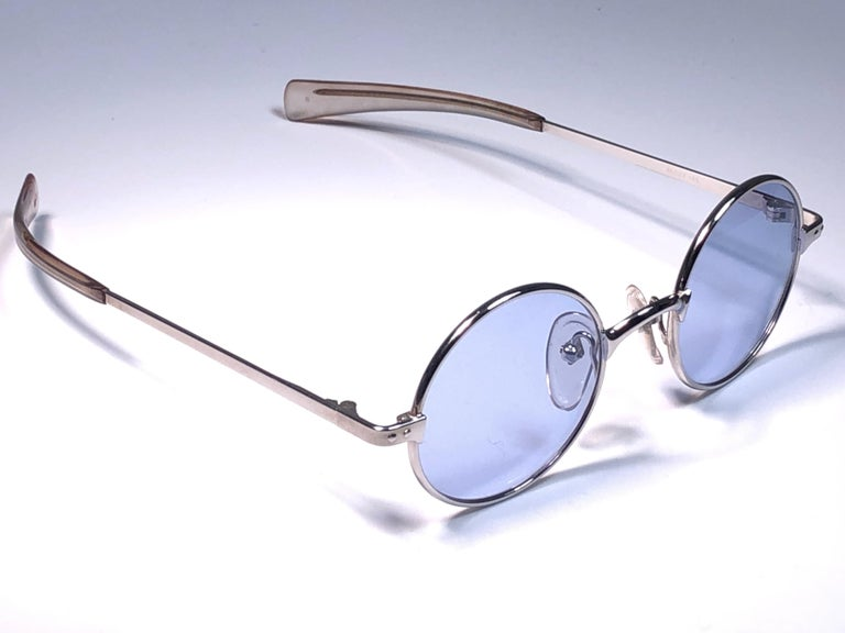 New Vintage Jean Paul Gaultier Junior 57 0173 silver frame. Spotless blue lenses. Design and produced in the 1900's a timeless and iconic piece. Minor sign of wear due to storage. A true fashion statement.  Front : 13 cms Lens : 4.5 cms Temples : 14