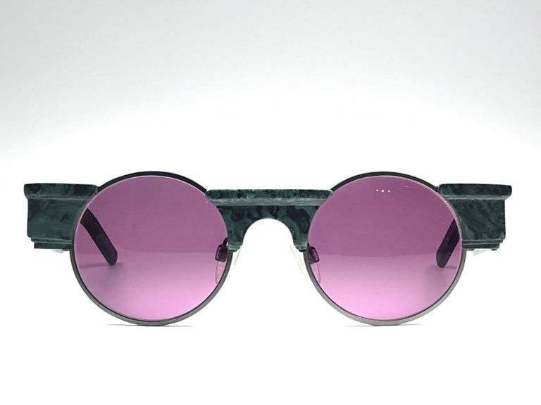 Striking pair of vintage Karl Lagerfeld Round dark green marbled sunglasses sporting a pair of purple lenses. Superb design emulating ancient greek architecture.   Front :  14 cms Lens Height : 4.5 cms Lens Width : 5 cms.   Although it has never