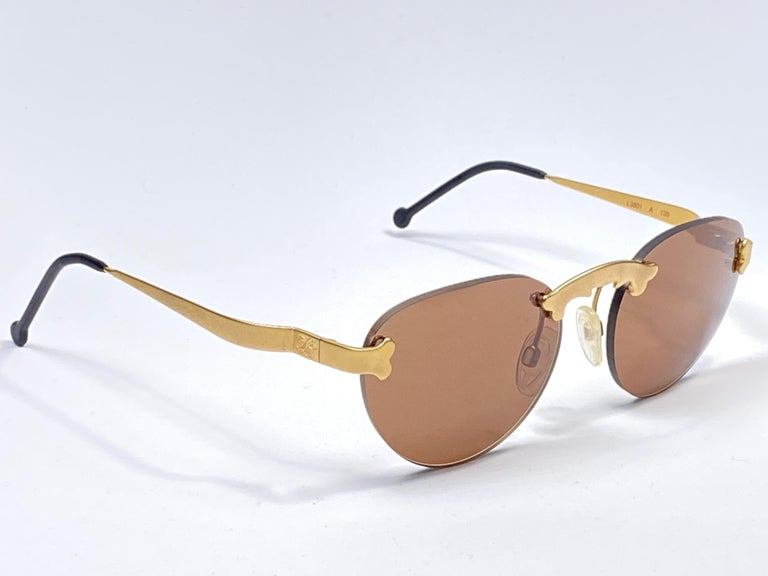 Astounding pair of vintage Karl Lagerfeld gold oval rimless sunglasses sporting a spotless pair of amber lenses. Baroque distinctive nose bridge design.   New, never used or displayed this pair of vintage karl lagerfeld is a showstopper. a true