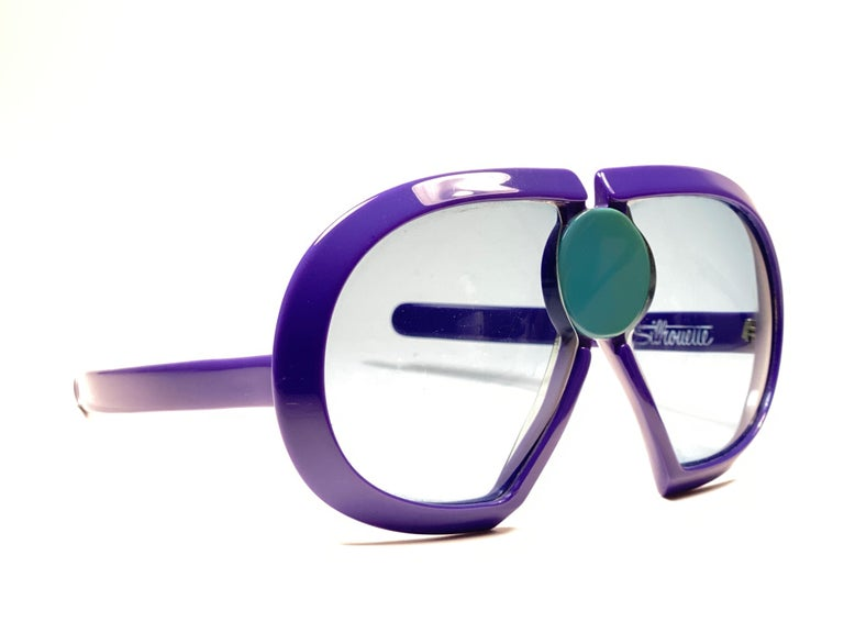 New Vintage Collector Item Silhouette Futura 571 purple thick frame with blue ornament holding a spotless pair of light blue lenses.     Designed by Dora Demmel in 1973, this rare piece is the epitome of avant garde & futuristic eye wear