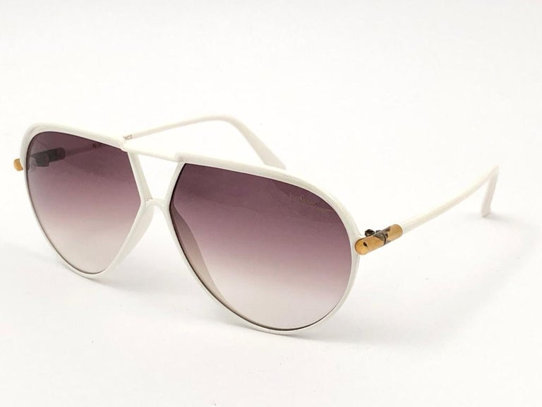Beautiful and stylish YSL sunglasses. White aviator frame holding a pair of double gradient lenses with beautiful old Cassandre logo. This pair show minor sign of wear due to storage on the gold details, Please study the pictures.  A great