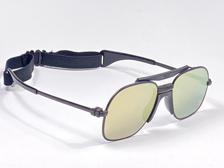 New vintage Zeiss sports oversized black matte frame with flat gold lenses and sports cord.   Made in West Germany.  This item is new and unworn but may show minor sign of wear due to storage.  MESUREMENTS:  FRONT : 14 CMS  LENS HEIGHT : 5 CMS  LENS