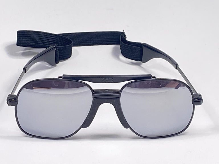 New vintage Zeiss sports oversized black matte frame with full mirror lenses and sports cord.   Made in West Germany.  This item is new and unworn but may show minor sign of wear due to storage.  MESUREMENTS:  FRONT : 14 CMS  LENS HEIGHT : 5