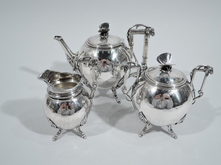 Aesthetic sterling silver tea set. Made by John Wendt for Ball, Black & Co. in New York, circa 1865. This set comprises teapot, creamer, and sugar. Each: Globular body on four monopodium hoof supports. High bracket handle with threaded and beaded